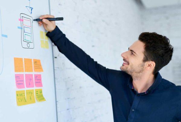 Man using a whiteboard for app design