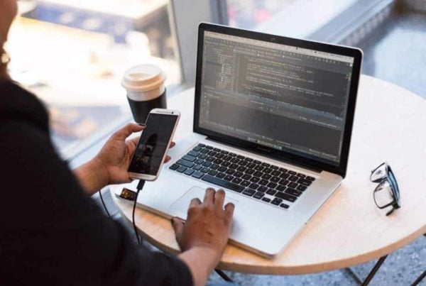 App development business woman using a mobile phone and coding on a MacBook